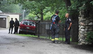 A firefighter and a policeman confer at the scene of a lightning strike that caused injuries at 9300 Moore Road in Indianapolis Saturday afternoon, June 29, 2013. Indianapolis police say three children were injured at a summer camp on the north side of Indianapolis by the lightning strike. (AP Photo/The Indianapolis Star, Rob Goebel)