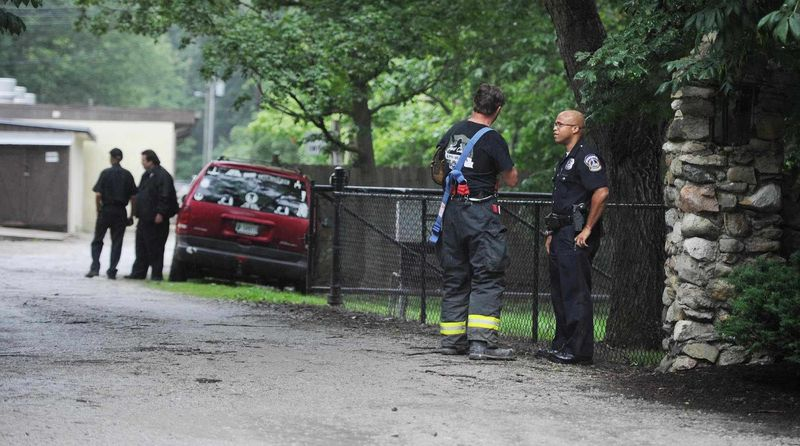 A firefighter and a policeman confer at the scene of a lightning strike that caused injuries at 9300 Moore Road in Indianapolis Saturday afternoon, June 29, 2013. Indianapolis police s