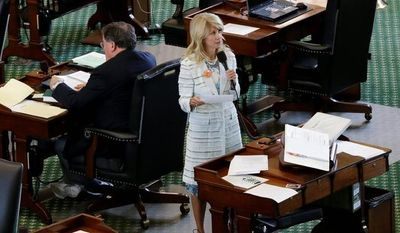 ** FILE ** In this June 26, 2013, file photo, Texas state Sen. Wendy Davis, Fort Worth Democrat, stands in pink tennis shoes on a nearly empty Senate floor as she filibusters in an effort to kill an abortion bill in Austin. (Associated Press)
