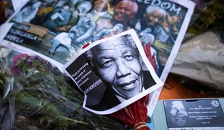Photos, flowers and good wishes laid in support of former South African President Nelson Mandela at the entrance of the Mediclinic Heart Hospital where Nelson Mandela is being treated in Pretoria, South Africa, Tuesday, July 2, 2013. Mandela remained in a critical condition on Tuesday. (AP Photo/Markus Schreiber)
