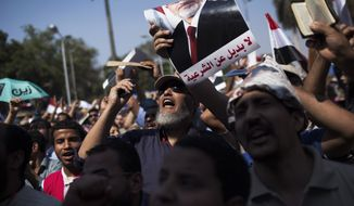 """Egyptians chant slogans supporting Islamist President Mohammed Morsi during a rally near Cairo University in Giza, Egypt, on July 2, 2013. With a military deadline for intervention ticking down, protesters seeking the ouster of Egypt's Islamist president sought to push the embattled leader further toward the edge with another massive display of people power. Arabic on the poster reads, """"no alternative to legitimacy."""" (Associated Press)"""