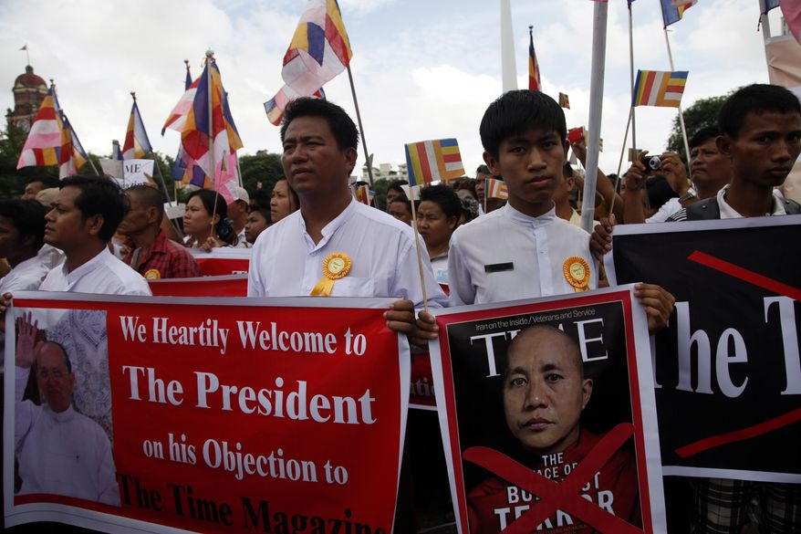 """Myanmar demonstrators hold banners in support of President Thein Sein's objections to a Time magazine cover article titled """"The Face of Buddhist Terror,"""" at City Hall in Yangon, Myanmar, on Sunday, June 30, 2013. Myanmar authorities banned the July 1 issue of the newsweekly because the article, which is about a Buddhist monk accused of fueling recent religious violence in the country. (AP Photo/Khin Maung Win)"""