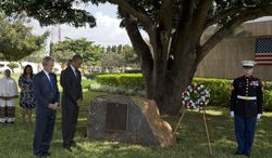 Former President George W. Bush and President Obama observe a moment of silence during a wreath-laying ceremony on Tuesday, July 2, 2013, to honor the victims of the U.S. Embassy bombing in Dar es Salaam, Tanzania. Mr. Obama is traveling in Tanzania on the final leg of his three-country tour in Africa. (AP Photo/Evan Vucci)