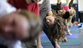 **FILE** Students hold their position during a yoga class at Capri Elementary School in Encinitas, Calif., on Dec. 11, 2012. (Associated Press)