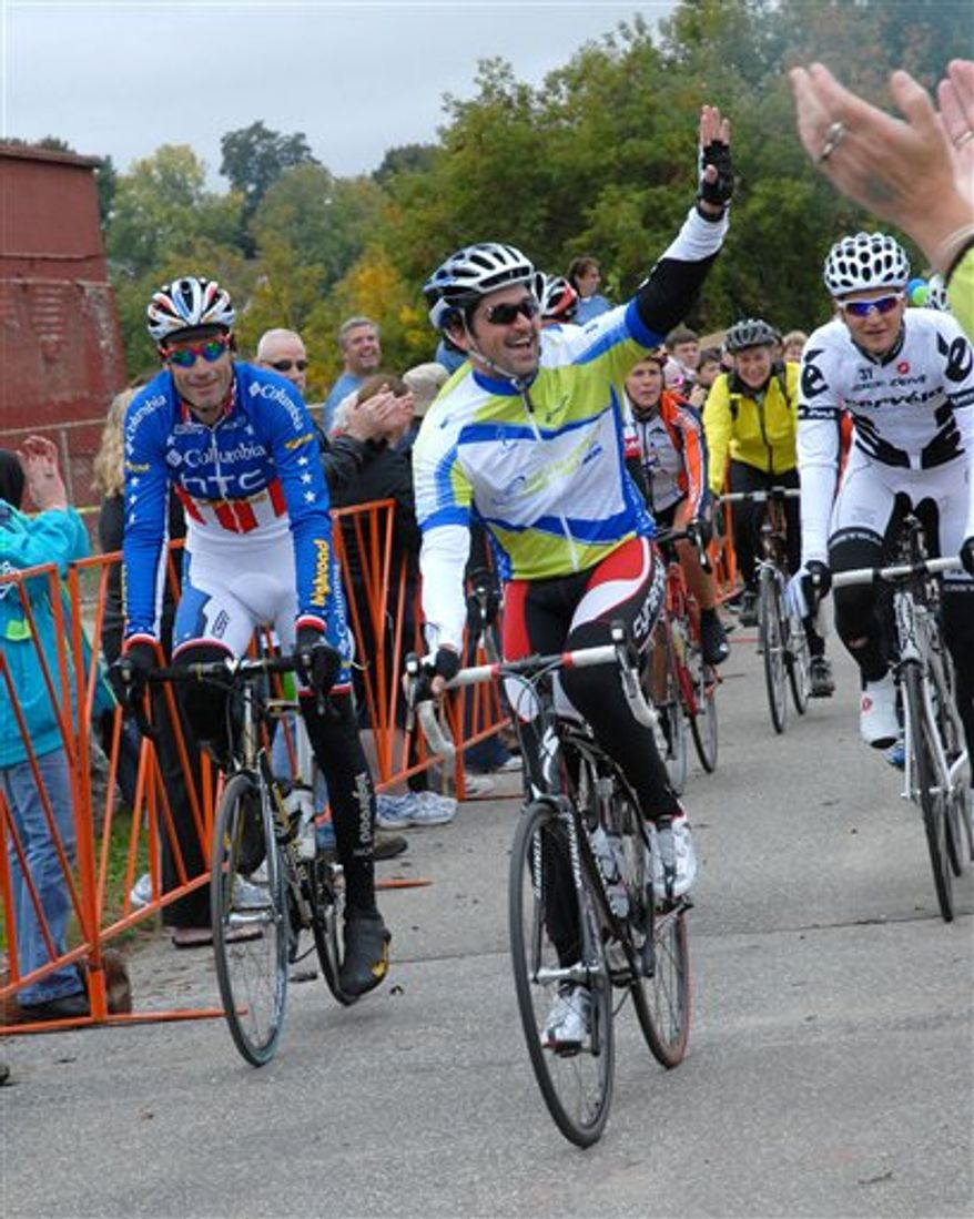 **FILE** Patrick Dempsey waves to onlookers as he crosses the finish line alongside professional cyclists George Hincapie (left) and Ted King at the 2009 Dempsey Challenge in Lewiston, Maine. (PRNewsFoto/The Patrick Dempsey Center for Cancer Hope & Healing, Tracey Twitchell-Pray)