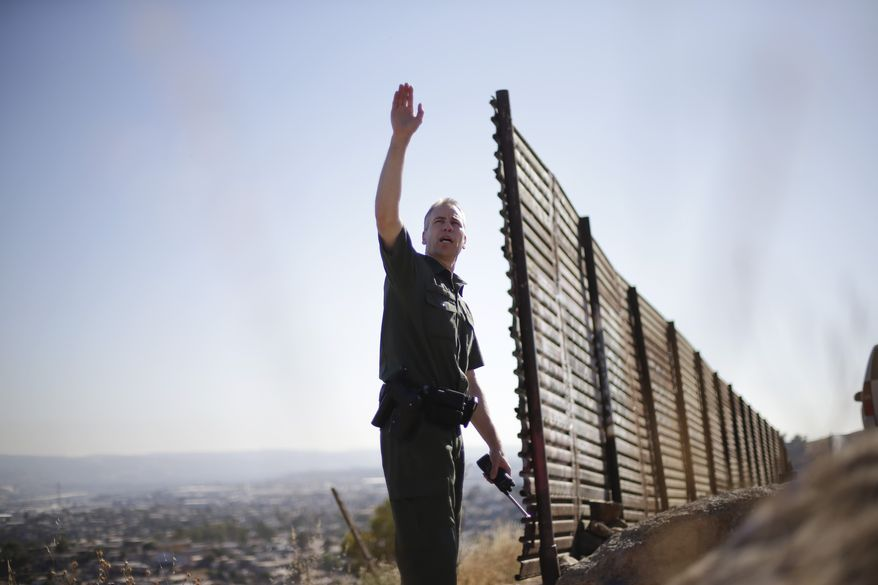 **FILE** U.S. Border Patrol agent Jerry Conlin looks out over Tijuana, Mexico, along the old border wall along the U.S.-Mexico border on June 13, 2013, where it ends at the base of a hill in San Diego. (Associated Press)