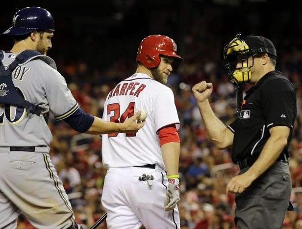 Bryce Harper walks back to the dugout after striking out to open the ninth inning on Wednesday night. Harper was one of four starting position players who went hitless in the Nationals' 4-1 loss to the Brewers. (Associated Press photo)