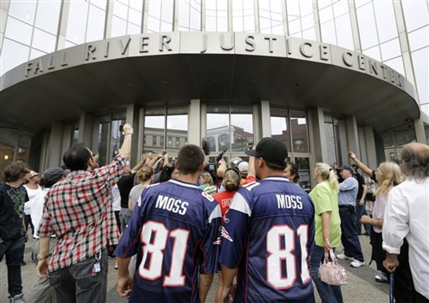 **FILE** Interested bystanders and media members crowd around the entrance to the Fall River Justice Center after a bail hearing was held for former New England Patriots football player Aaron Hernandez in Fall River Superior Court Thursday, June 27, 2013 in Fall River, Mass. Hernandez, charged with murdering Odin Lloyd, a 27-year-old semi-pro football player, was denied bail. (AP Photo/Elise Amendola)