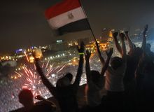 Egyptians wave a national flag July 3, 2013, as fireworks light the sky over Tahrir Square in Cairo, where hundreds of thousands opponents of Egyptian President Mohammed Morsi celebrate the Egyptian military's ouster of Morsi, who was Egypt's first freely elected leader but drew ire with his Islamist leanings. (Associated Press)