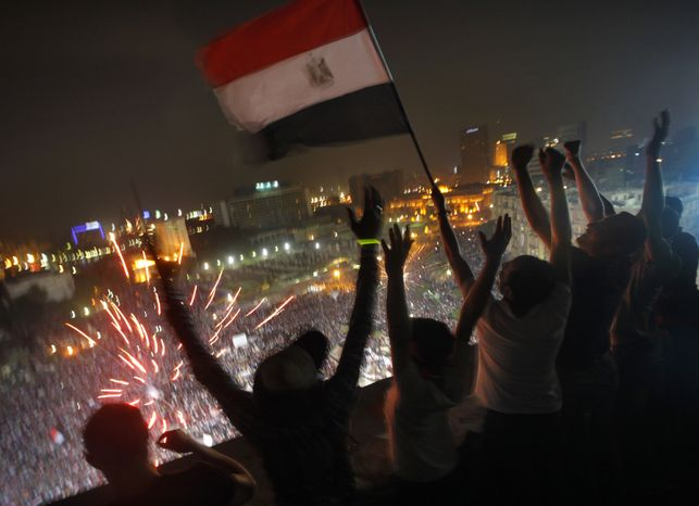Egyptians wave a national flag July 3, 2013, as fireworks light the sky over Tahrir Square in Cairo, where hundreds of thousands opponents of Egyptian President Mohammed Morsi celebrate the Egyptian military's ouste