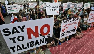 ** FILE ** Pakistani workers of political party Muttahida Qaumi Movement (MQM), hold placards during a protest to condemn the killing of foreign tourists by militants, in Karachi, Pakistan, Sunday, June 23, 2013.  (AP Photo/Fareed Khan)