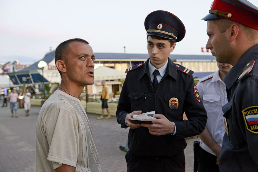 In this photo taken Tuesday, May 21, 2013, police officers check documents while patrolling in the Black Sea resort of Sochi, southern Russia. Police, security and medical personnel in Sochi have conducted dozens of drills to train for potential threats. (AP Photo/Artur Lebedev)