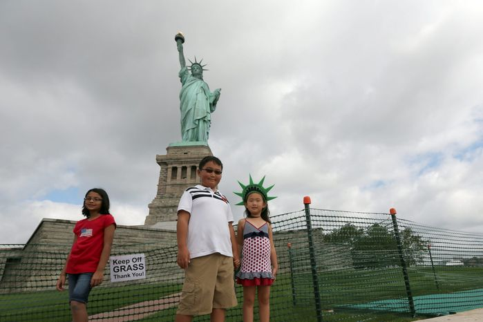 Children pose for pictures at the base of the Statue of Liberty on Thursday in New York. The Statue of Liberty finally reopened months after Superstorm Sandy swamped its little island in New York Harbor. (Associated Press)
