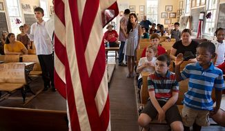 Children take an oath of citizenship during a ceremony at the old school house in Old Sacramento, Calif. on Wednesday. Today's children become tomorrow's workers and future retirees. Most Americans end up getting more back in benefits than they pay into the entitlement system, meaning the immigrants being added now could become liabilities later on. (Associated Press)