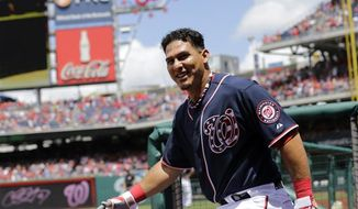Washington Nationals Wilson Ramos comes out of the dugout to acknowledge the fans after his three-run homer during the seventh inning of an MLB National League baseball game against the Milwaukee Brewers at Nationals Park Thursday, July 4, 2013, in Washington. The Nationals won 8-5. (AP Photo/Alex Brandon)