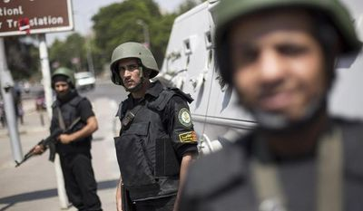 Egyptian police special forces stand guard beside an armored vehicle, protecting a bridge between Tahrir Square and Cairo University, where Muslim Brotherhood supporters have gathered, in Giza, Egypt, Wednesday, July 3, 2013. (AP Photo/ Manu Brabo)