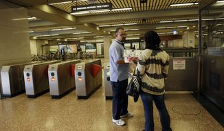 ** FILE ** BART station agent Mark Madrigal helps a customer at the Lake Merritt station in Oakland, Calif., Friday, June 28, 2013. (AP Photo/Marcio Jose Sanchez)