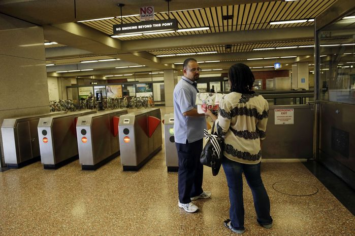 ** FILE ** BART station agent Mark Madrigal helps a customer at the Lake Merritt station in Oakland, Calif., Friday, Ju