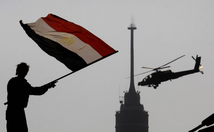 An opponent of Egypt's ousted President Mohammed Morsi waves a national flag as a military helicopter flies over Tahrir Square in Cairo on Friday, July 5, 2013. (AP Photo/Amr Nabil)