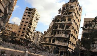 **FILE** In this July 3, 2013, citizen journalism image provided by Lens Young Homsi, which has been authenticated based on its contents and other AP reporting, buildings damaged by Syrian government airstrikes and shelling are seen in the Jouret al-Chiyah neighborhood of Homs, Syria. (Associated Press)