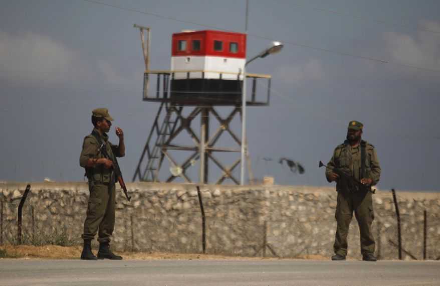 Palestinian Hamas security guards stand near an Egyptian watch tower on the border with Egypt in Rafah, southern Gaza Strip, Friday, July 5, 2013. (AP Photo/Hatem Moussa)