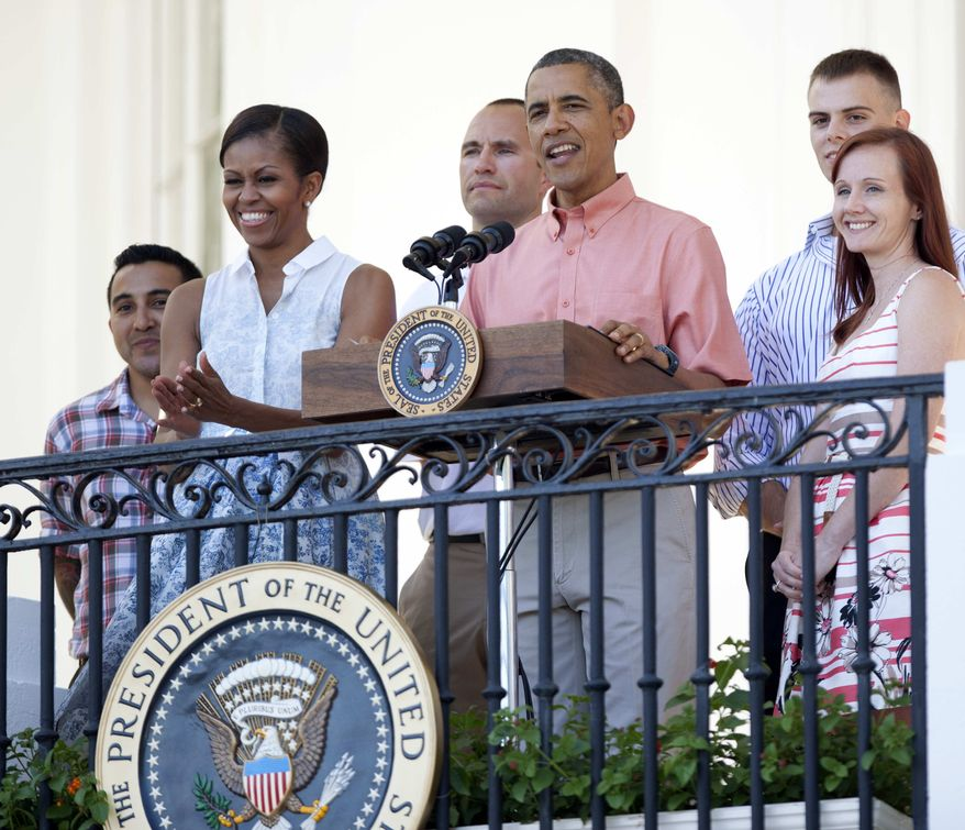 President Barack Obama, third from right, with first lady Michelle Obama, second from left, and members of the military, speaks during a Fourth of July celebration on the South Lawn of the White House in Washington, Thursday, July 4, 2013. (AP Photo/Manuel Balce Ceneta)