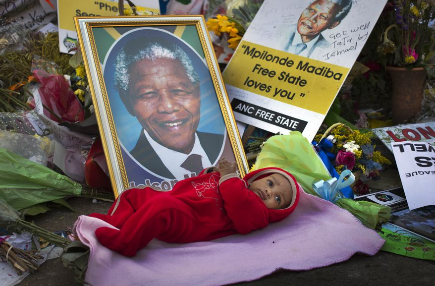 Oamohetswe Mabitsela, four months old, is placed next to a picture of former South African President Nelson Mandela by his mother for her to take a photograph of him with her camera phone, outside the Mediclinic Heart Hospital in Pretoria, South Africa, where Mandela is being treated. (Associated Press)