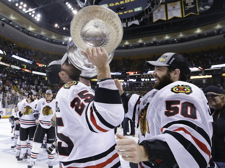 Chicago Blackhawks left wing Viktor Stalberg (25) hoists the Stanley Cup alongside goalie Corey Crawford (50) after the Blackhawks beat the Boston Bruins in Game 6 of the NHL hockey Stanley Cup Finals in Boston June 24, 2013. (Associated Press)