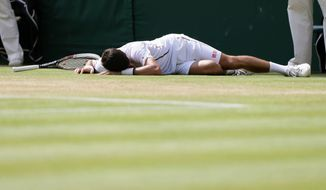 Novak Djokovic of Serbia lies on the court after playing a return to Juan Martin Del Potro of Argentina during their men's singles semifinal match at the All England Lawn Tennis Championships in Wimbledon, London, Friday, July 5, 2013. (AP Photo/Alastair Grant)