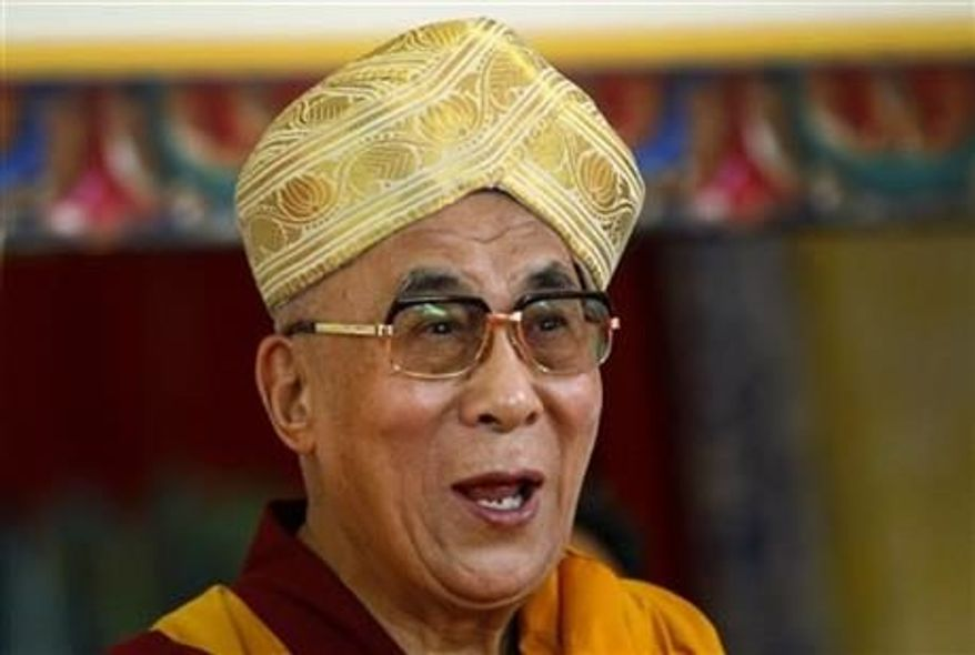 Tibetan spiritual leader the Dalai Lama gestures after he was presented the traditional headgear during an event organized to celebrate his 78th birthday at a Tibetan Buddhist monastery in Bylakuppe, about 137 miles southwest of Bangalore, India, Saturday, July, 6, 2013. (Associated Press)