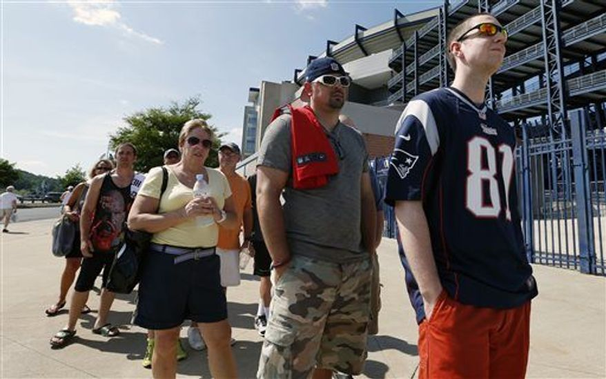 Mike Davies, right, of Norfolk, Mass., wears his New England Patriots Aaron Hernandez football jersey one last time while waiting in an exchange line outside Gillette Stadium in Foxborough, Mass., Saturday, July 6, 2013. Fans may trade an Aaron Hernandez jersey with his name on it they purchased for one of another player on the NFL team. The team released Hernandez after he was arrested for allegedly orchestrating the death of Odin Lloyd. (AP Photo/Michael Dwyer)