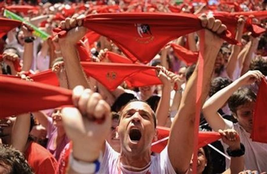 """Revelers hold up traditional red neckties as tens of thousands of people packed Pamplona's main square in Pamplona, northern Spain on Saturday, July 6, 2013 to celebrate the start of Spain's most famous bull-running festival with the annual launch of the """"chupinazo"""" rocket. (AP Photo/Alvaro Barrientos)"""