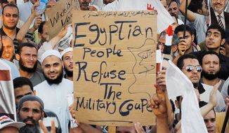 Members of the Muslim Brotherhood and other supporters of ousted President Mohammed Morsi protest near Cairo University on Sunday as tensions mount between Islamists and the U.S.-backed secular military. (Associated Press)