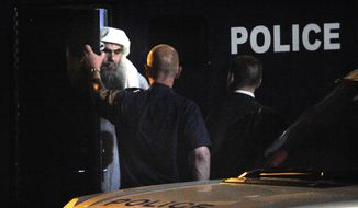 Radical Muslim cleric Abu Qatada (left) prepares to board a private flight bound for Jordan at RAF Northolt in London on Sunday, July 7, 2013. Abu Qatada was deported to Jordan to face terror charges, ending over a decadelong battle to remove a man described as a key al Qaeda operative in Europe. (AP Photo/Ministry of Defense, Sgt. Ralph Merry)