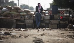 A supporter of ousted Egyptian President Mohammed Morsi stands guard at a barricade near Cairo University, where protesters have installed their camp, in Giza, Egypt, southwest of Cairo, on Sunday, July 7, 2013. (AP Photo/Manu Brabo)