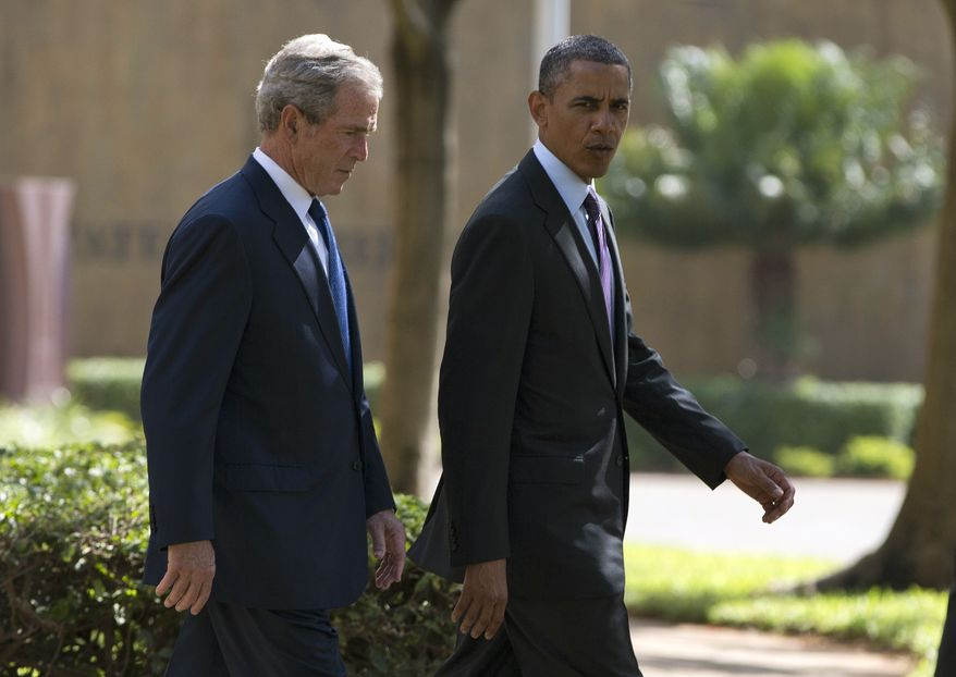 President Obama (right) walks with former President George W. Bush during a wreath-laying ceremony on Tuesday, July 2, 2013, to honor the victims of the U.S. Embassy bombing in Dar es Salaam, Tanzania. Mr. Obama was traveling in Tanzania on the final leg of his three-country tour in Africa. (AP Photo/Evan Vucci)