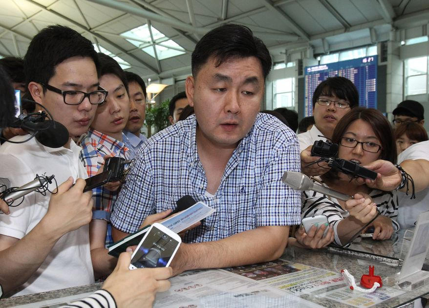 Geum Jae-kook (center), a relative of a passenger injured when an Asiana Airlines plane crashed Saturday in San Francisco, checks in at the Incheon International Airport in Incheon, South Korea, on Sunday, July 7, 2013, before boarding his flight for the United States to meet his family member. (AP Photo/Ahn Young-joon)