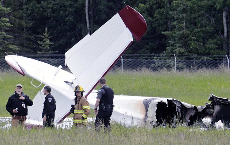 Police and emergency personnel stand near the remains of a fixed-wing aircraft that was engulfed in flames Sunday July 7, 2013, at the Soldotna Airport in Soldotna, Alaska. There were no survivors. (AP Photo/Peninsula Clarion, Rashah McChesney)