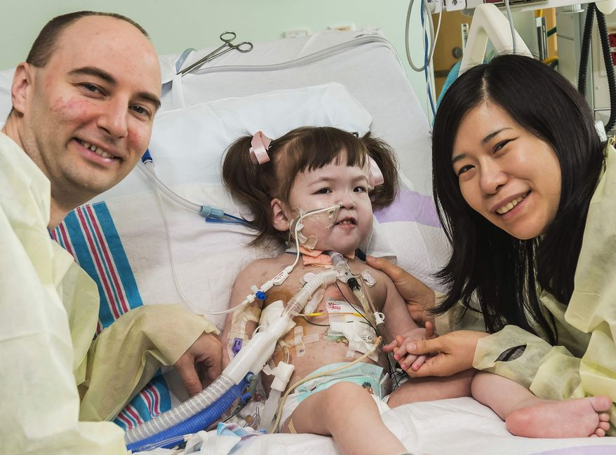 ** FILE ** In this April 26, 2013, file photo provided by OSF Saint Francis Medical Center in Peoria, Ill., Darryl Warren and Lee Young-mi visit with their 2-year-old daughter Hannah Warren in a post-op room at Children's Hospital of Illinois in Peoria after having received a new windpipe in a landmark transplant operation April 9, 2013. Hannah died Saturday, July 6, 2013. She was the youngest patient in the world to benefit from the experimental treatment. (AP Photo/OSF Saint Francis Medical Center, Jim Carlson, File)