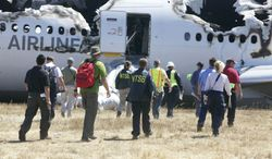 In this image provided by the NTSB, investigators examine the wreckage at the scene of the Asiana Airline crash Sunday July 7, 2013. The Asiana flight crashed upon landing Saturday, July 6, at San Francisco International Airport, and two of the 307 passengers aboard were killed. (AP Photo/NTSB)
