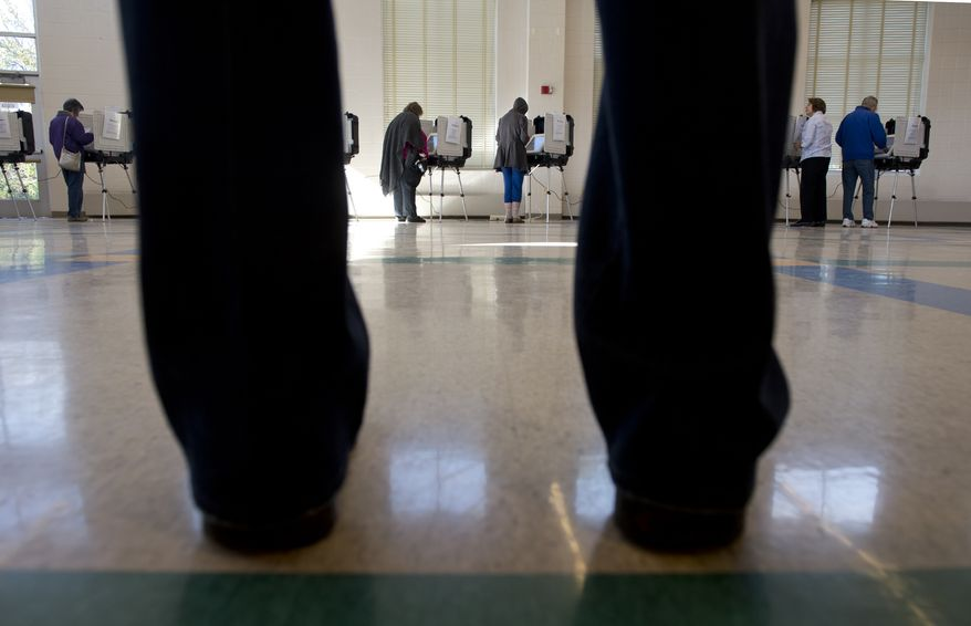 While one man waits for an election official to bring him to an available voting machine, other Marylanders cast their ballots at Winston Churchill High School in Potomac, Md. on Election Day, Tuesday, Nov. 6, 2012. (Barbara L. Salisbury/The Washington Times)