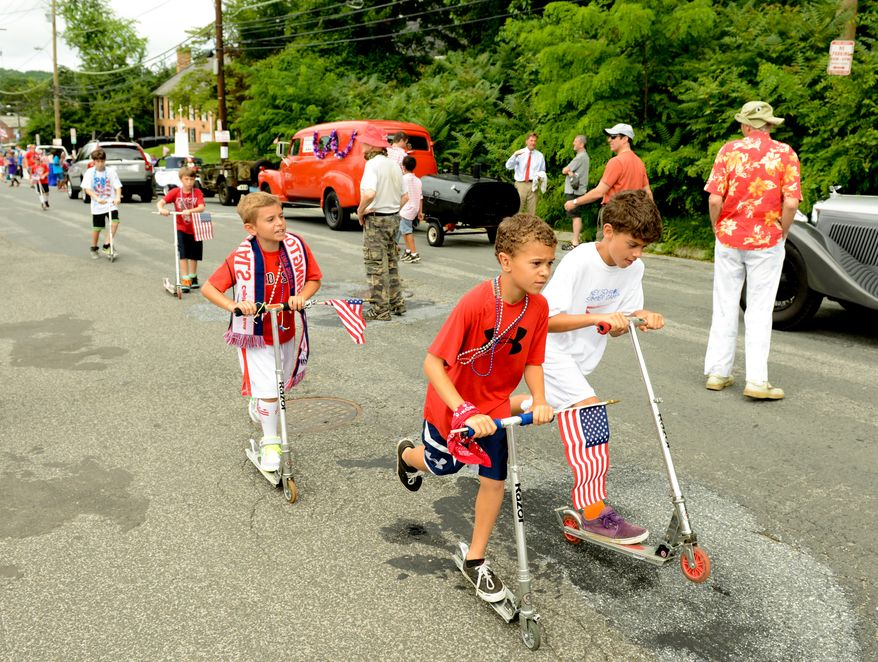 Children ride scooters along parade vehicles as the Palisades July 4th Parade gets ready to begin, Washington, D.C., Thursday, July 4, 2013. (Andrew Harnik/The Washington Times)