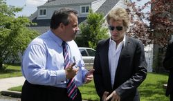 Singer Jon Bon Jovi (right), listens to New Jersey Gov. Chris Christie on July 8, 2013, as they walk in Sayreville, N.J. Bon Jovi is giving $1 million to help the band's home state recover from Superstorm Sandy. (Associated Press)