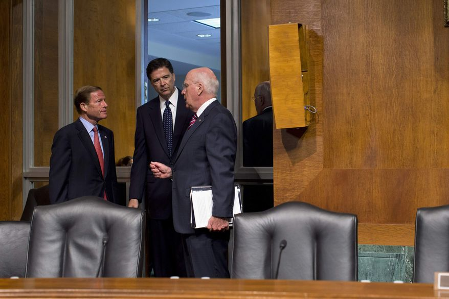 FBI Director nominee James Comey, center, talks Senate Judiciary Committee Chairman Sen. Patrick Leahy, D-Vt., right, and committee member Sen. Richard Blumenthal, D-Conn., on Capitol Hill in Washington, Tuesday, July 9, 2013, prior to the start of the committee's hearing on Comey's nomination. (AP Photo/Evan Vucci)