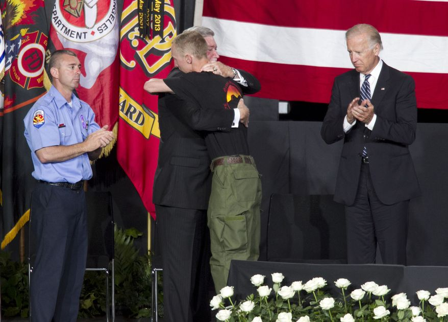 "Brendan McDonough (center right), the sole surviving member of the Granite Mountain Hotshots crew, hugs Harold A. Schaitberger, general president of the International Association of Firefighters, as Vice President Joseph R. Biden and Dan Bates, Prescott Chapter Vice President of United Yavapai Firefighters Association, Local 3066, look on during the ""Our Fallen Brothers"" memorial service for the 19 fallen firefighters at Tim's Toyota Center in Prescott Valley, Ariz., on Tuesday, July 9, 2013. (Associated Press/The Arizona Republic)"
