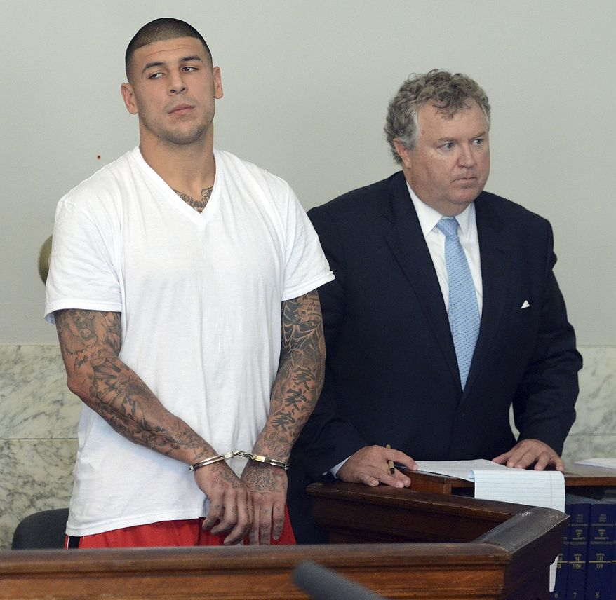 """FILE - In this June 26, 2013 file photo, former New England Patriots tight end Aaron Hernandez, left, stands with his attorney Michael Fee, right, during arraignment in Attleboro District Court in Attleboro, Mass. A police search of a secret """"flop house"""" rented by Hernandez turned up boxes of ammunition and clothing police believe could be evidence in the murder case against him, according to court documents. (AP Photo/The Sun Chronicle, Mike George, Pool, File)"""