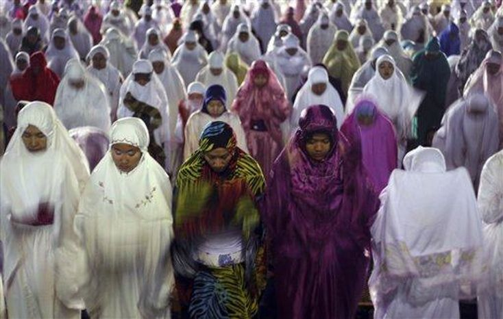 """Muslim women perform an evening prayer called """"tarawih,"""" marking the first eve of the holy fasting month of Ramadan, at a mosque in Denpasar, Bali, Indonesia, on Tuesday, July 9, 2013. During Ramadan, the holiest month in Islamic calendar, Muslims refrain from eating, drinking, smoking and sex from dawn to dusk. Fasting during Ramadan is one of the Five Pillars of Islam. (AP Photo/Firdia Lisnawati) ** FILE **"""