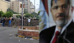 Supporters of ousted Egyptian President Mohammed Morsi protest as army soldiers guard at the Republican Guard building in Nasr City in Cairo on July 10, 2013. (Associated Press)
