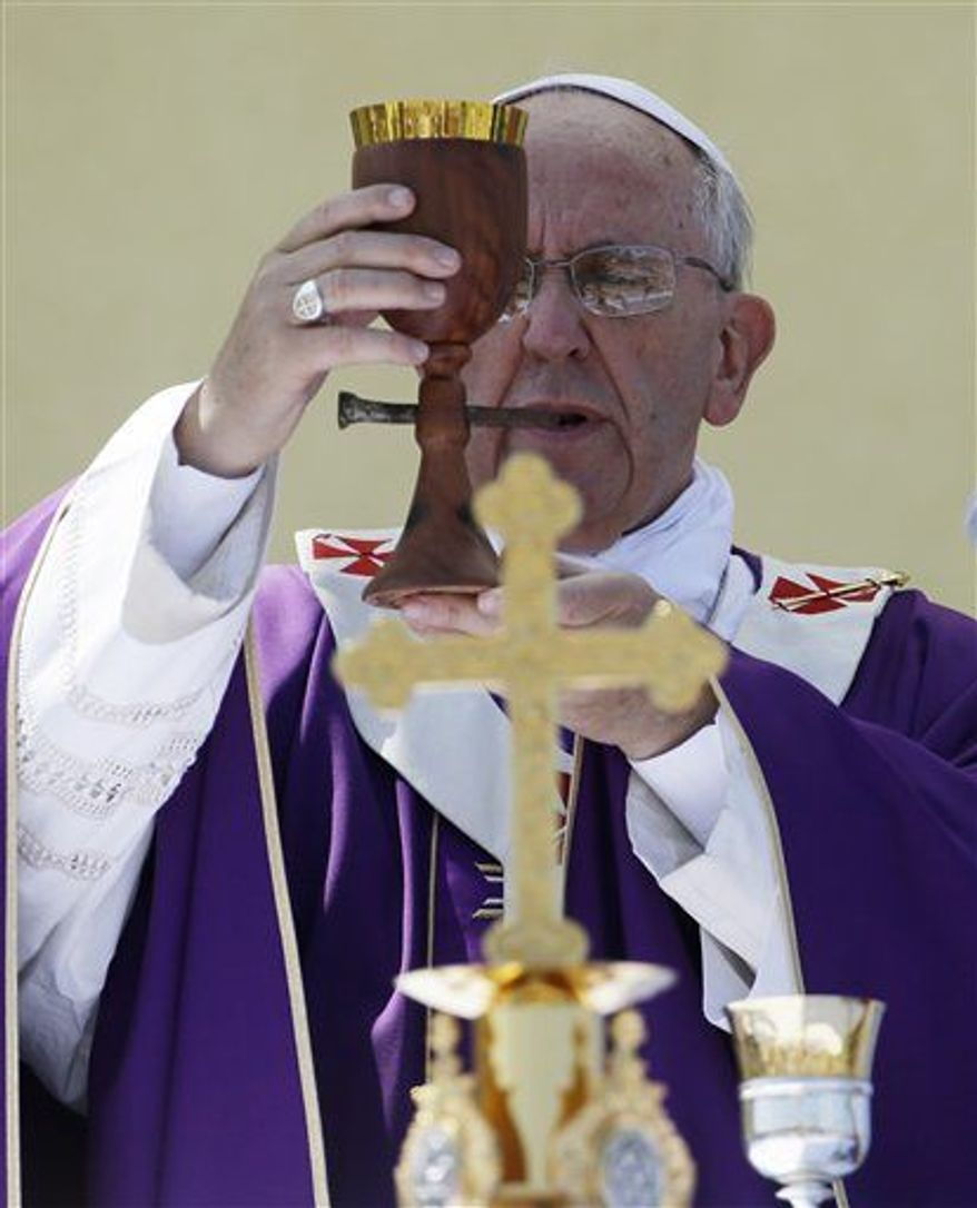 ** FILE ** Pope Francis celebrates a Mass with a chalice made from recycled wood from broken migrant boats, during his visit to the island of Lampedusa, southern Italy, July 8, 2013. (AP Photo/Gregorio Borgia)