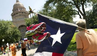 ** FILE ** Karen McCrocklin of Dallas carries a Texas flag with pink running shoes similar to those worn by state Sen. Wendy Davis during the previous week's filibuster during a pro-abortion rights rally at the state Capitol in Austin, Texas, on Monday, July 1, 2013. (AP Photo/Statesman.com, Jay Janner)